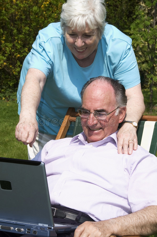 Retired couple. Using a laptop computer in the garden