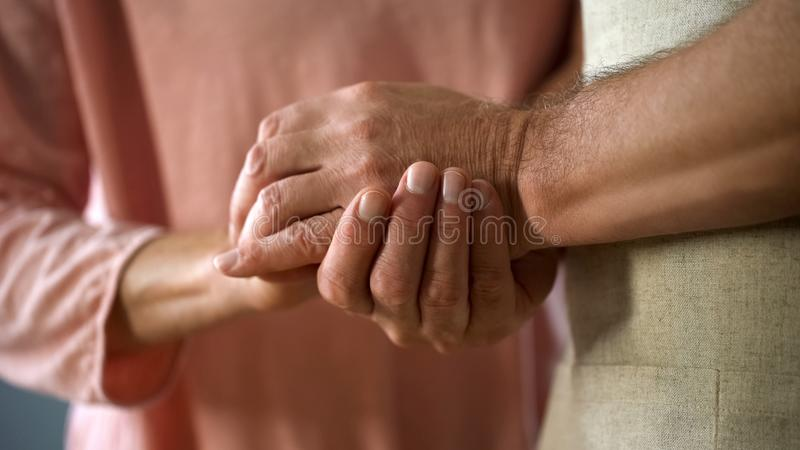 Retired couple holding hands, love connection, elderly husband and wife support stock images