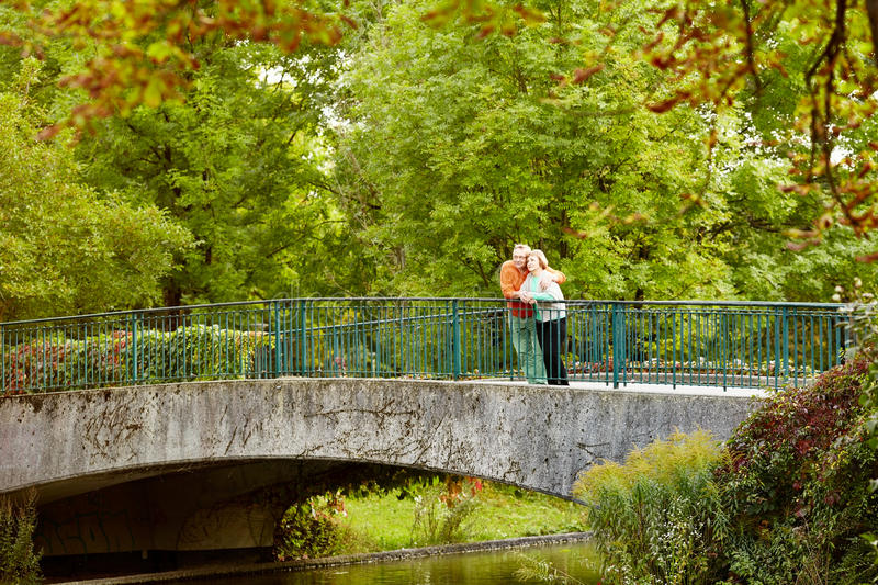 Retired couple hugging on bridge royalty free stock photo