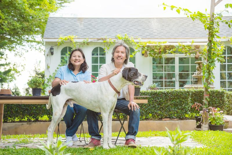 Retired couple sitting with dog in garden of their house stock images