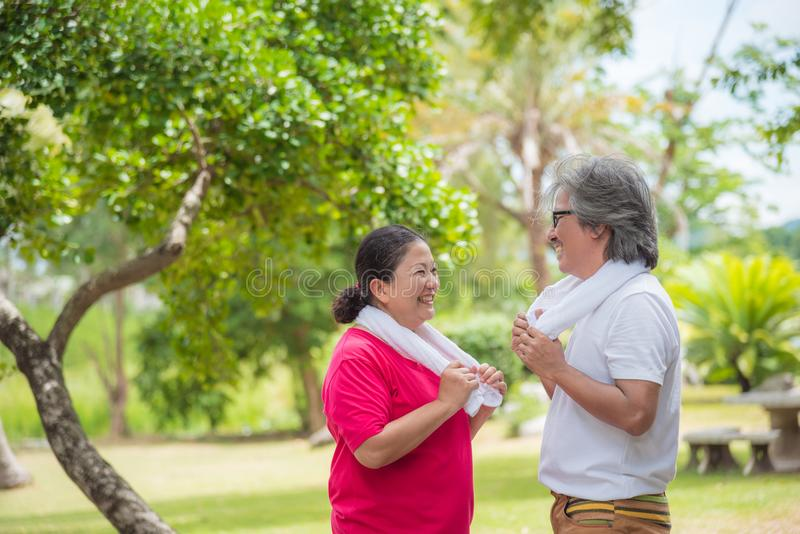 Retired couple talking with smile after walking in park royalty free stock images