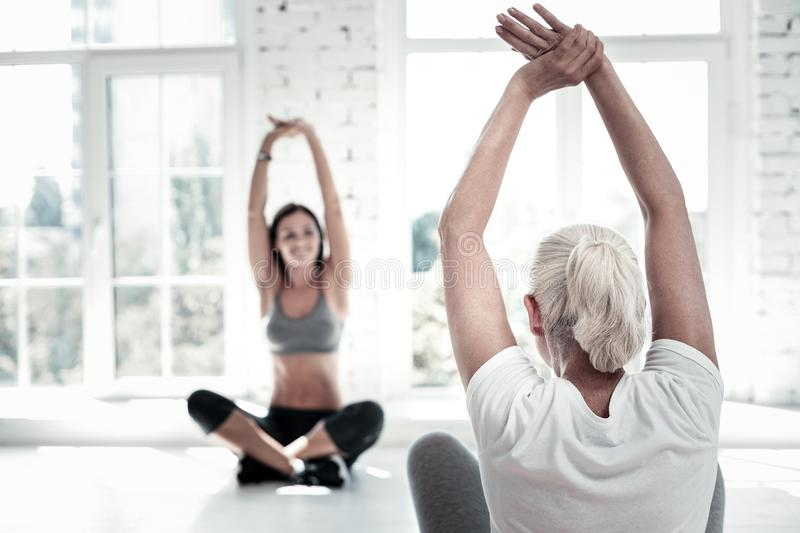 Retired lady training and stretching at fitness club stock photo