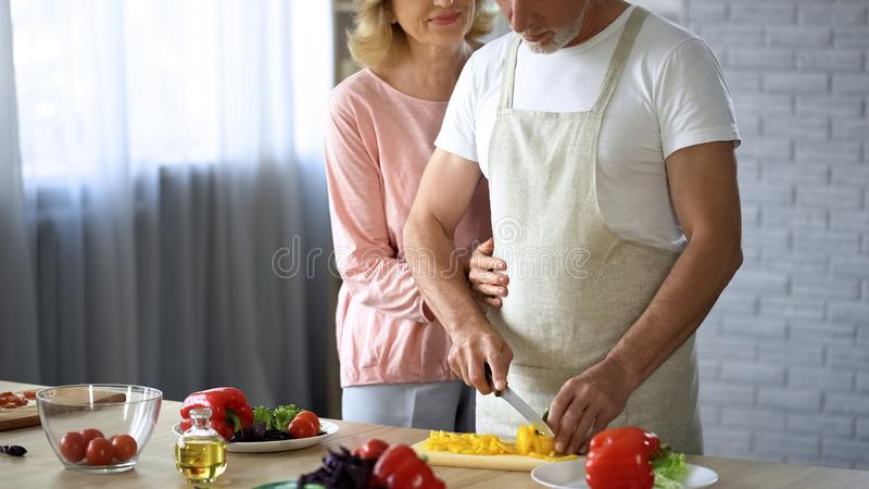 Retired male cooking salad, caring wife hugging husband, family support, help. Stock photo stock photo