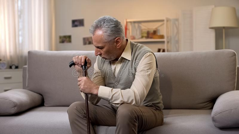 Retired man with cane sitting on sofa, loneliness and depression, problems royalty free stock photos