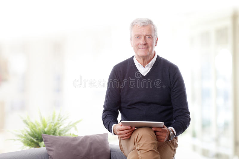 Retired man with digital tablet stock photo