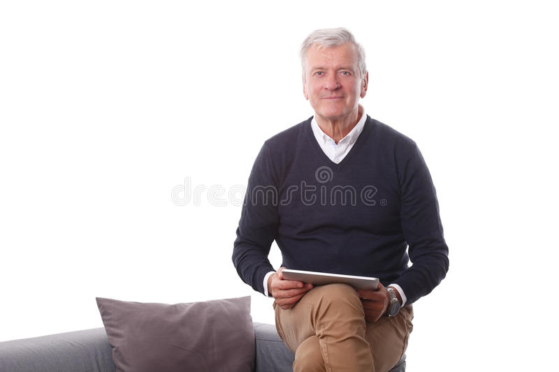 Retired man with digital tablet. Portrait of retired man holding in his hand a digital tablet while sitting at sofa in living room. Isolated on white background royalty free stock photography