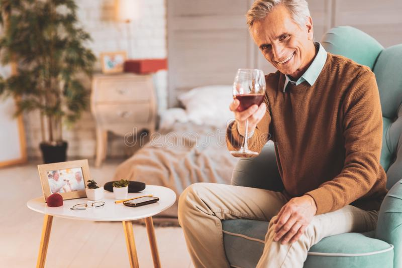 Retired man drinking wine celebrating his birthday. Birthday celebration. Retired happy man drinking red wine while celebrating his birthday royalty free stock images