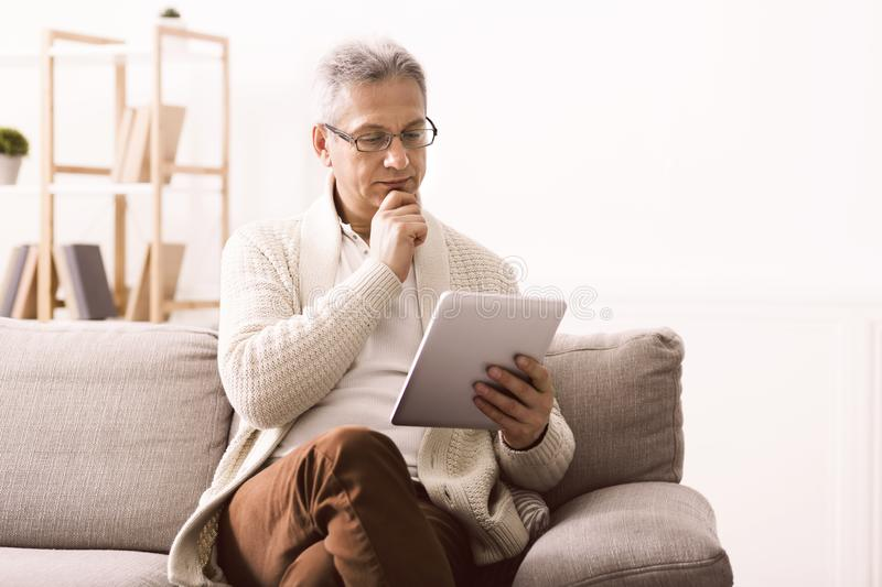 Retired man reading news on tablet at home royalty free stock photography