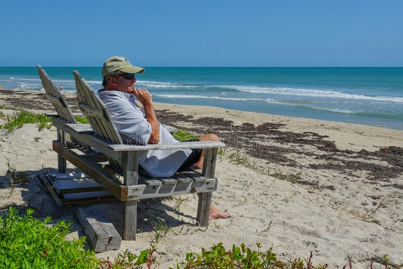 Retired man sitting on a chair overlooking the turquoise blue ocean stock photo