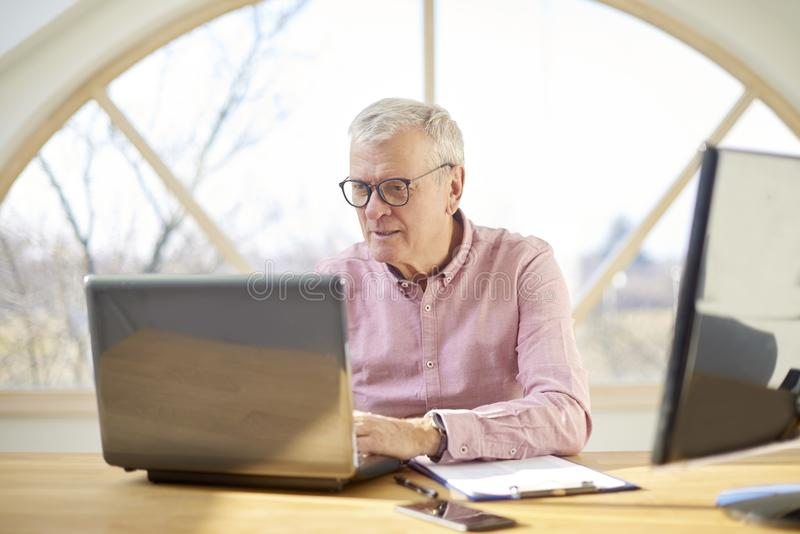 Senior buisnessman with laptop. Retired man wearing shirt and sitting at desk while working on laptop from home stock photo