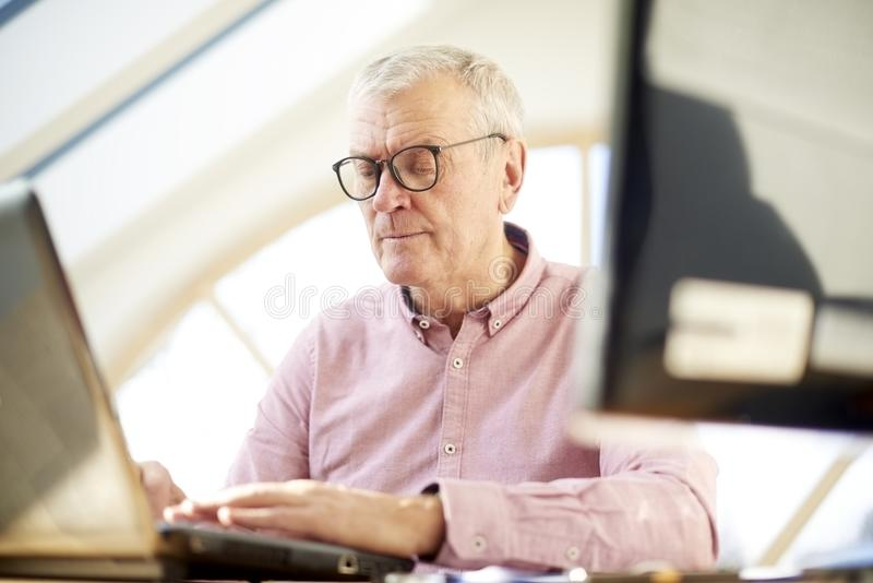 Senior buisnessman with laptop. Retired man wearing shirt and sitting at desk while working on laptop from home stock photography