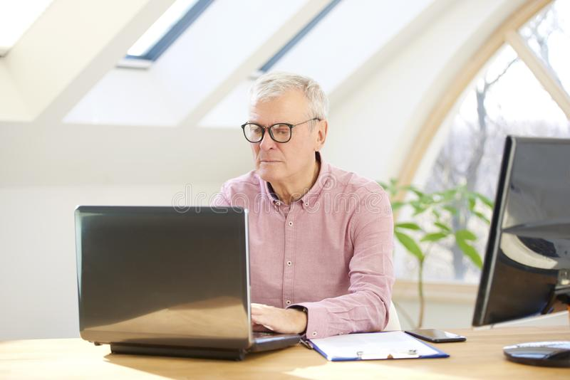 Senior buisnessman with laptop. Retired man wearing shirt and sitting at desk while working on laptop from home royalty free stock image
