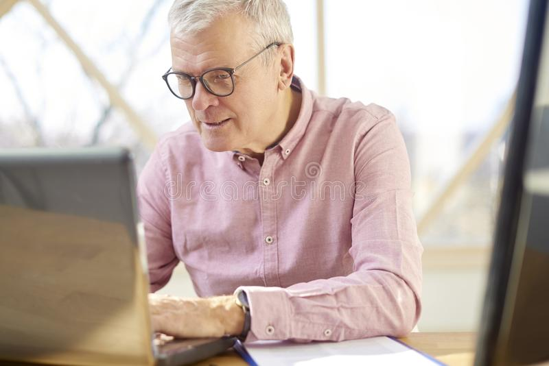 Senior buisnessman with laptop. Retired man wearing shirt and sitting at desk while working on laptop from home stock images