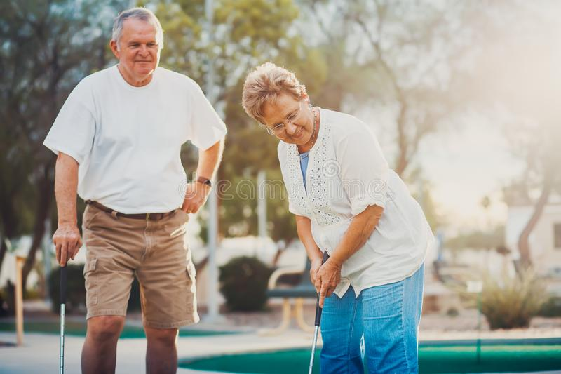 Retired married elderly couple playing mini golf together royalty free stock photos