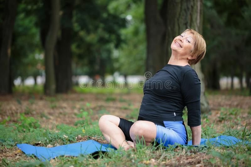Happy old yoga woman. Smiling mature lady on a mat on a park background. Healthy lifestyle concept. Copy space. royalty free stock photography