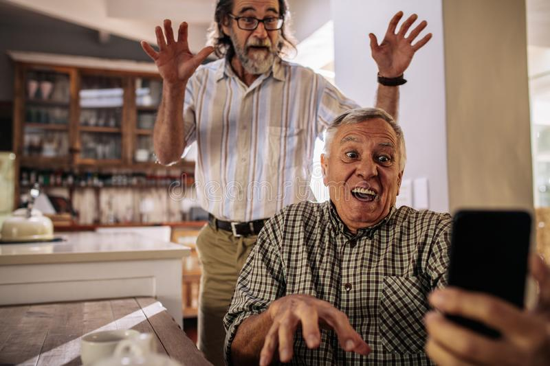 Retired men making funny faces while taking selfie royalty free stock photography