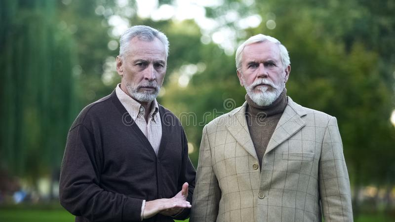 Retired men sadly looking in camera, poor quality of living for pensioners stock image