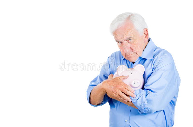 Retired old man holding a piggy bank, looking very serious and possessive of his savings