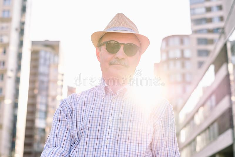 Retired senior hispanic man with hat standing and smiling. Retired senior hispanic man with hat and summer glasses standing and smiling at sunny day stock photo