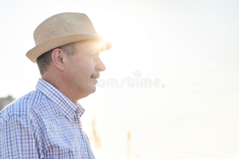 Retired senior hispanic man with hat standing and smiling. At sunny day. Profile view royalty free stock photo