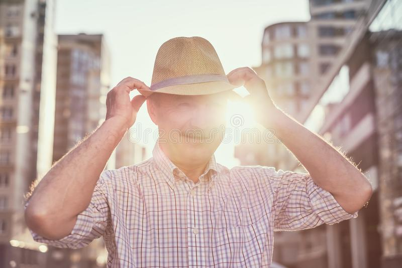Retired senior hispanic man with hat standing and smiling. At sunny day royalty free stock image