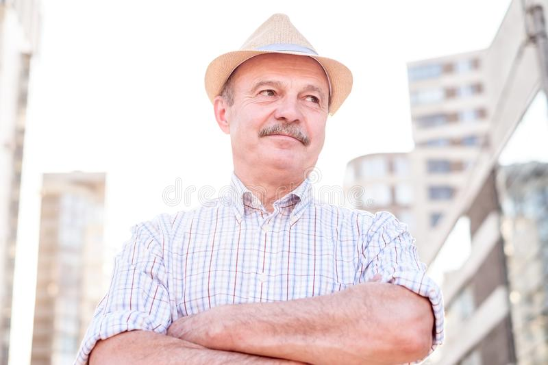 Retired senior hispanic man with hat standing and smiling. At sunny day stock images