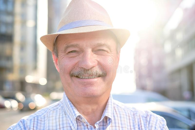 Retired senior hispanic man with hat standing and smiling. At sunny day royalty free stock photo
