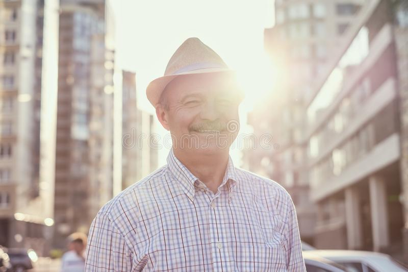 Retired senior hispanic man with hat standing and smiling. At sunny day royalty free stock photos