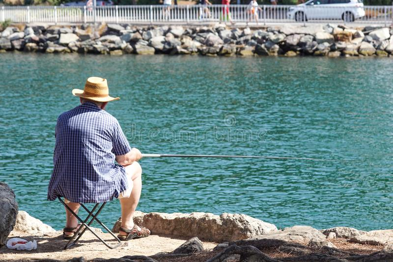 Retired senior man enjoys fishing from a pier into the river stock images