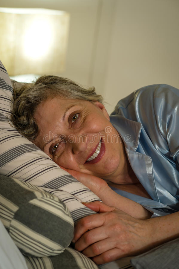 Retired smiling woman lying in bed. Looking at camera royalty free stock photo