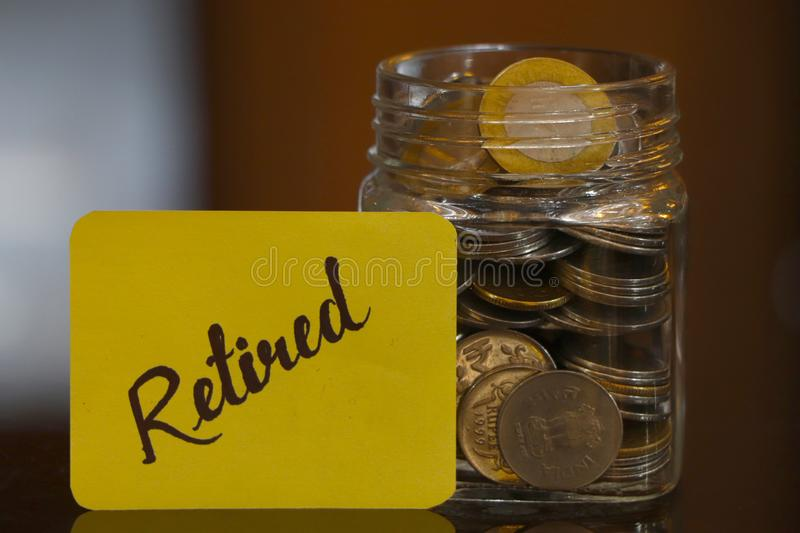 Retired. Money Jar. Retired text on a paper, a clear glass jar filed with coins stock images