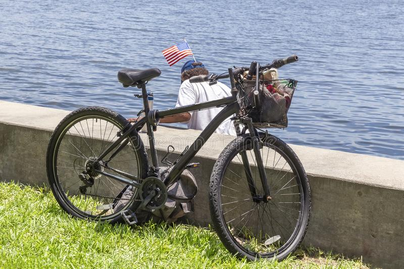 A retired veteran parks his bike next to the the seawall as he climbs over into shallow waters on the other side. An American flag attached to his hat flapping royalty free stock images