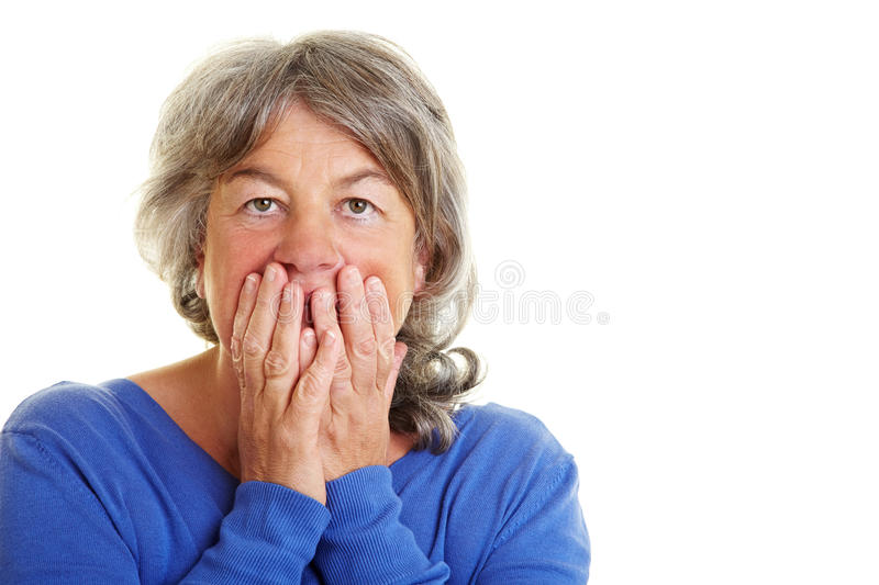 Retired woman is frightened. Frightened Retired woman holding hands over her mouth royalty free stock images