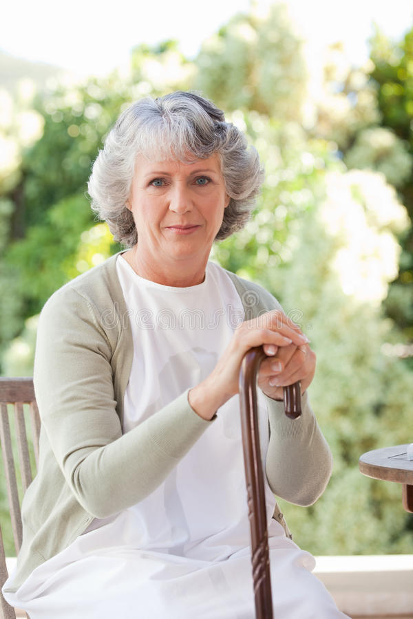 Retired woman with her walking stick royalty free stock image