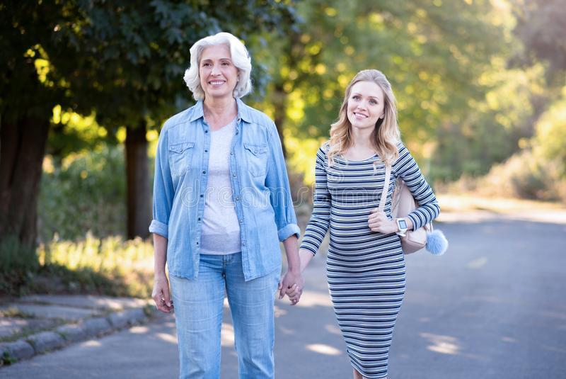 Retired woman holding hands with pregnant daughter in the park royalty free stock images