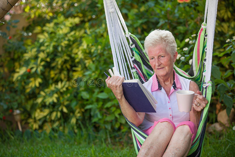 Retired woman reading royalty free stock photography