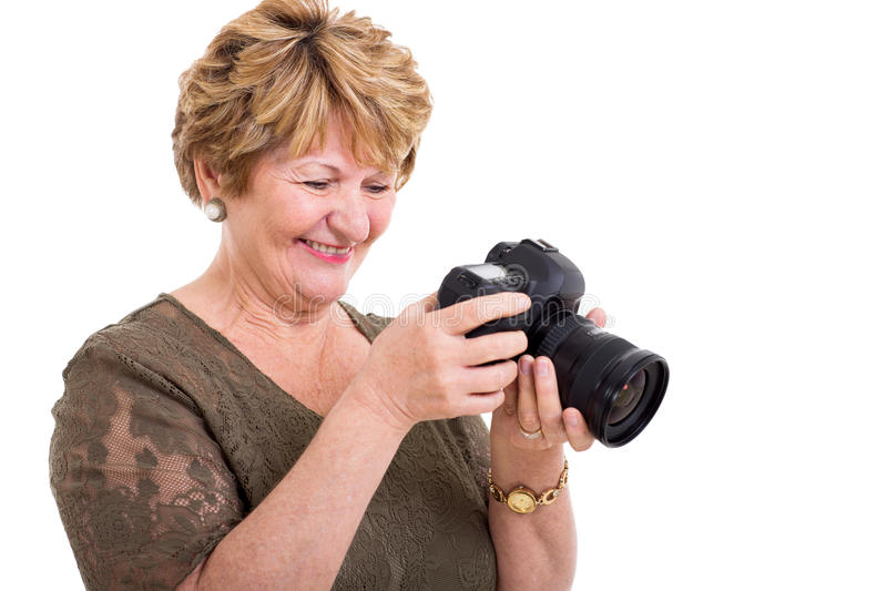 Retired woman SLR camera. Cheerful retired senior woman viewing photos on a digital SLR camera stock images