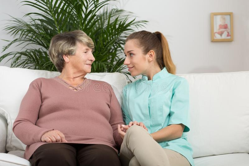 Retired woman talking with nurse. Picture of content retired women talking with young nurse stock photos