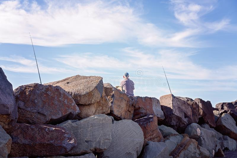 Retiree Fishing From Breakwater Rocks royalty free stock images