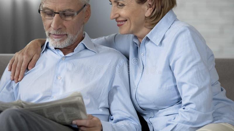 Retiree husband reading newspaper on sofa, woman beside hugging him, love royalty free stock photography