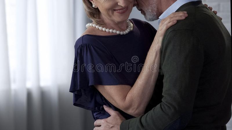 Retiree male and female dancing and hugging, lady smiling playfully, happy time stock image