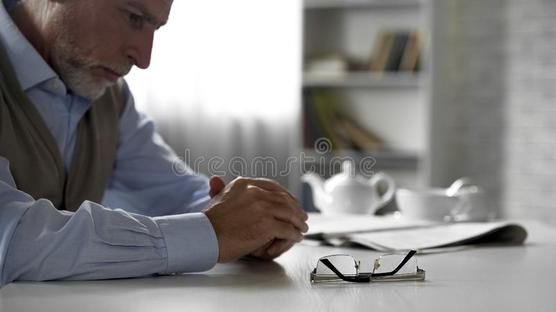 Retiree male sitting alone at kitchen table taken off his glasses, poor vision stock photography