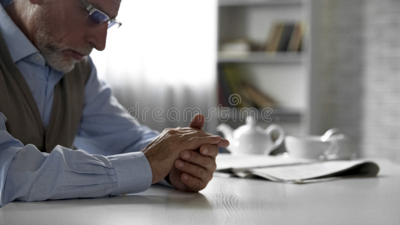 Retiree man sitting at table and looking at his hands, feeling depressed stock photography