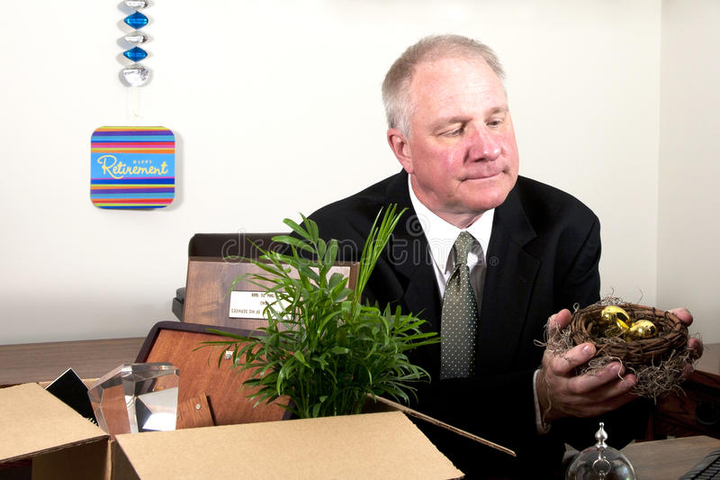 Retiree with Nest Egg. Senior man in a business suit sitting behind a desk holding nest egg with box of personal effects stock images