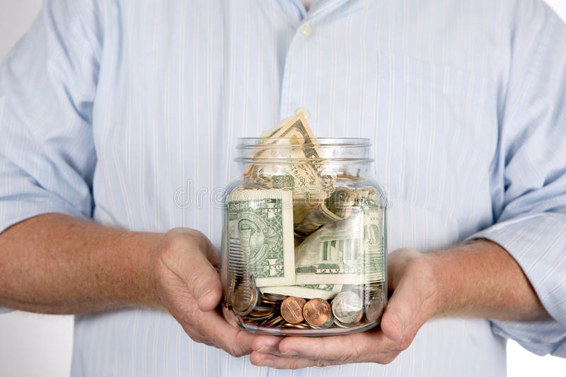 Retirees Retirement Piggy Bank Account. Retired man holding his retirement piggy bank money account in his hands in a glass jar stock photos