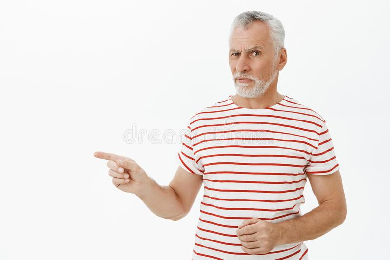 Retirement, age and people concept. Portrait of hesitant doubtful handsome old male with white beard in striped t-shirt. Raising eyebrow questioned pointing royalty free stock photos