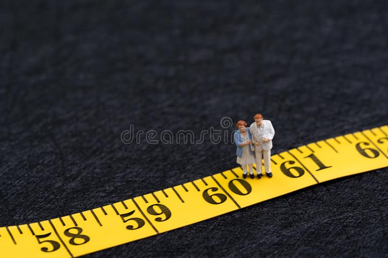 Retirement age, 60 years old age or senior citizen concept, happy miniature senior couple holding each other standing on number 60 royalty free stock photos