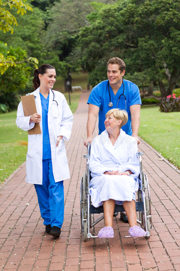 Retirement home. Young happy doctor, nurse and patient in retirement home royalty free stock image