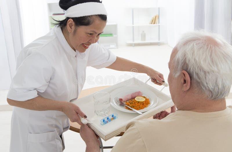RETIREMENT HOME CARE GIVER. Senior wman eats lunch at retirement home (care, home, elderly stock photo