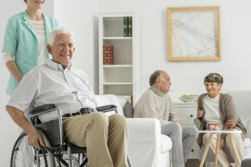 Retirement home with elder man. Retirement home with elder men on a wheelchair royalty free stock photos